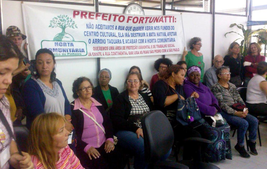 Comunidade e voluntários da horta compareceram para pressionar delegados.
