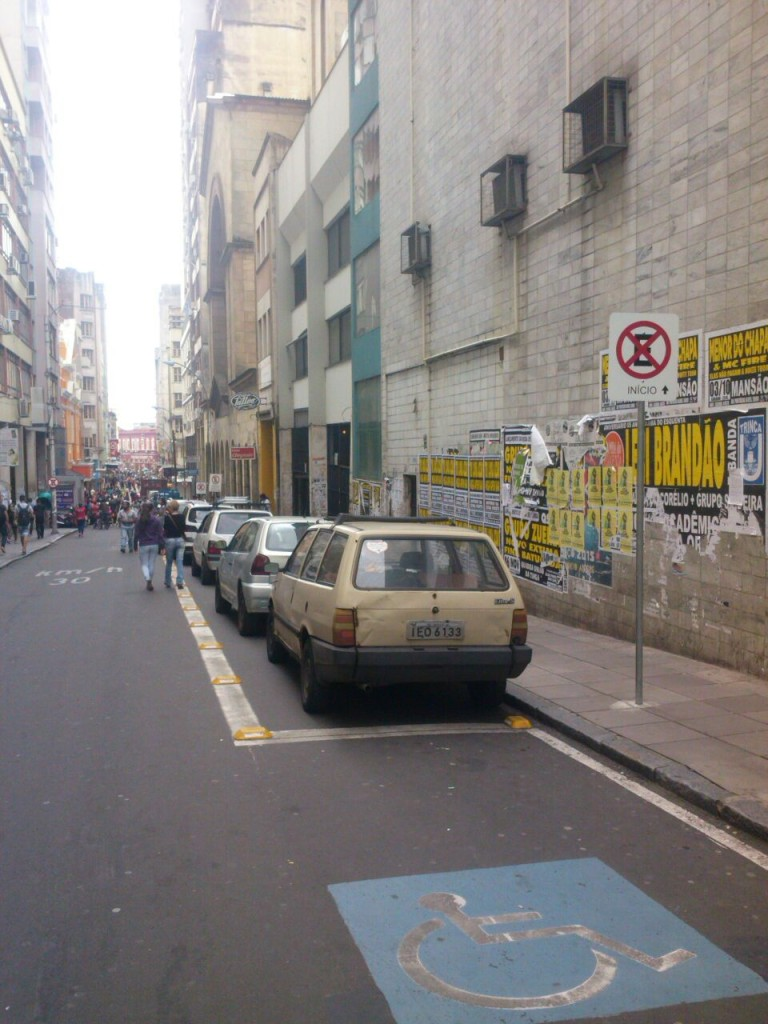 Carros estacionados sobre área exclusiva de pedestres.